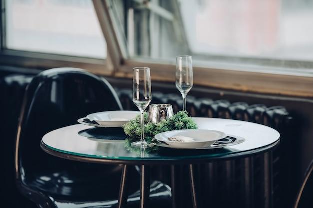 Widok na pięknie zdobiony okrągły stół z naturalną gałązką jodły, świecą, dwoma fletami, talerzami na tle klasycznej sofy w nowoczesnym mieszkaniu.