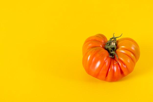 Widok na piękny czerwony malinowy pomidor na żółtym tle
