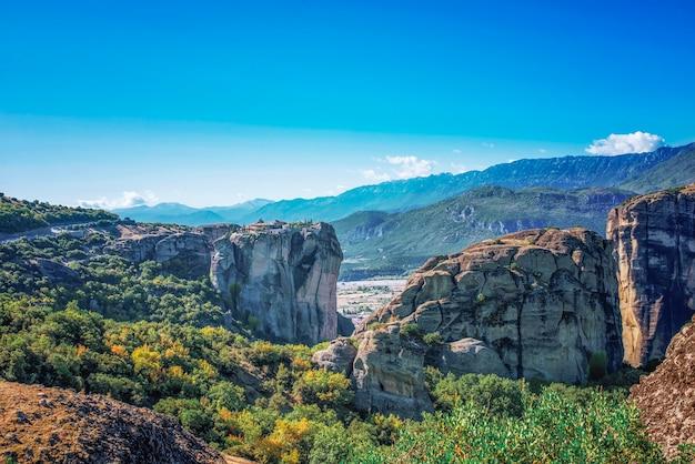 Widok na piękny krajobraz zielonych gór z drzewami i krzewami w słoneczny dzień i błękitne niebo bez chmur