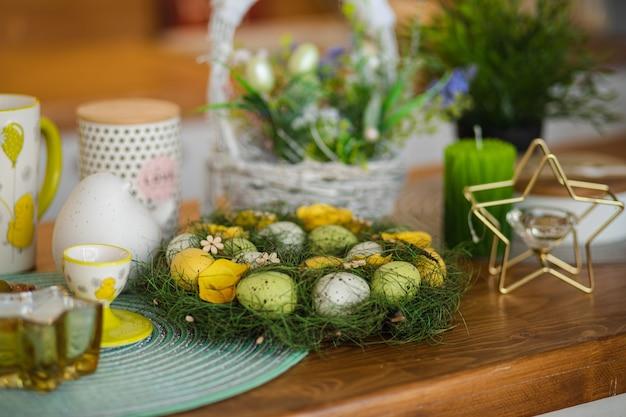 Widok na piękny wieniec wielkanocny ozdobiony malowanymi jajkami i trawą. drewniany licznik z koszykiem wielkanocnym w niewyraźne tło.
