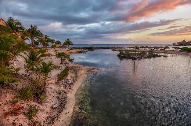 Widok na plażę puerto aventuras na riwierze majów w meksyku pokrytą mrocznym niebem z kontrastami niebieskiego, fioletowego i pomarańczowego.