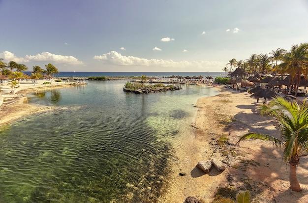 Widok na plażę puerto aventuras w meksyku, podczas zachodu słońca w piękny letni dzień.