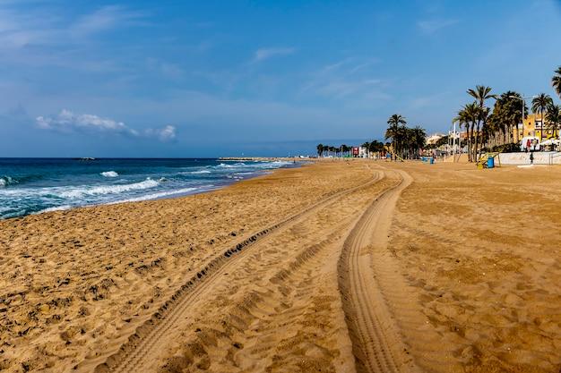 Widok na plażę villajoyosa ze śladami opon na piasku, alicante, hiszpania.