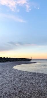 Widok na plażę w liverpoolu o zachodzie słońca, rzędy falochronów, wielka brytania