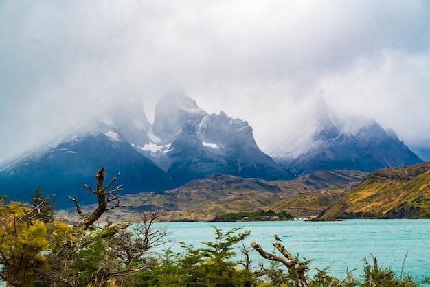 Widok na pokryte mgłą cuernos del paine i jezioro pehoe w parku narodowym torres del paine, chile