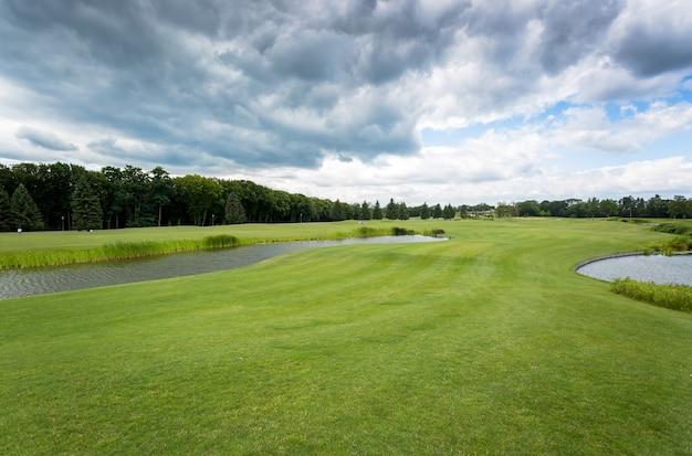 Widok na pole golfowe w zimny dzień z deszczowymi chmurami na niebie