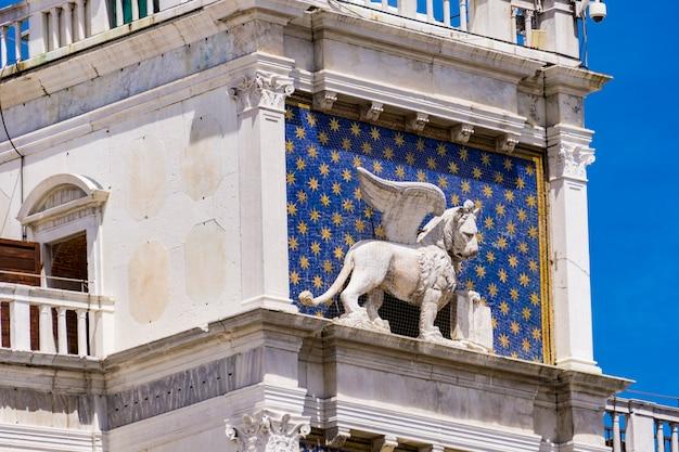 Widok na pomnik skrzydlatego lwa na wieży zegarowej na piazza di san marco w wenecji, włochy