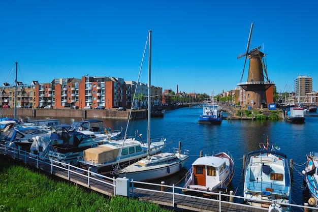 Widok na port delfshaven i stary młyn zbożowy de destilleerketel rotterdam, holandia