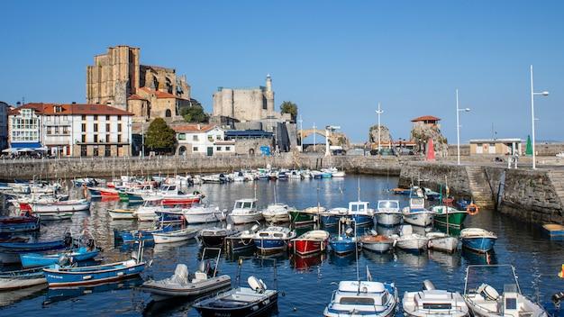 Widok na port i miasto castro urdiales w słoneczny dzień.
