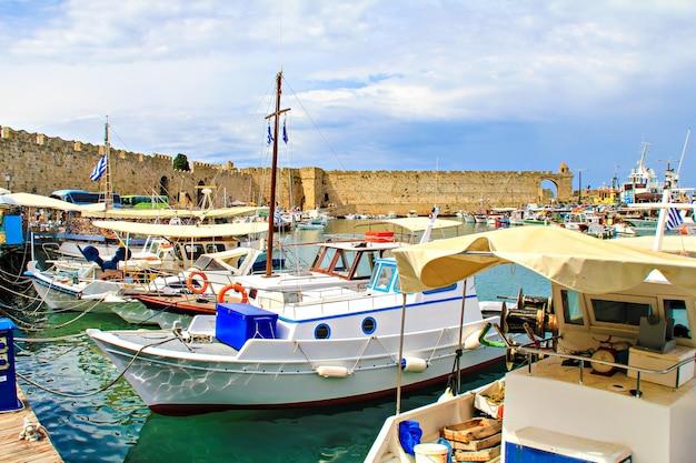 Widok na port na rodos, grecja. łodzie motorowe i starożytne mury miejskie