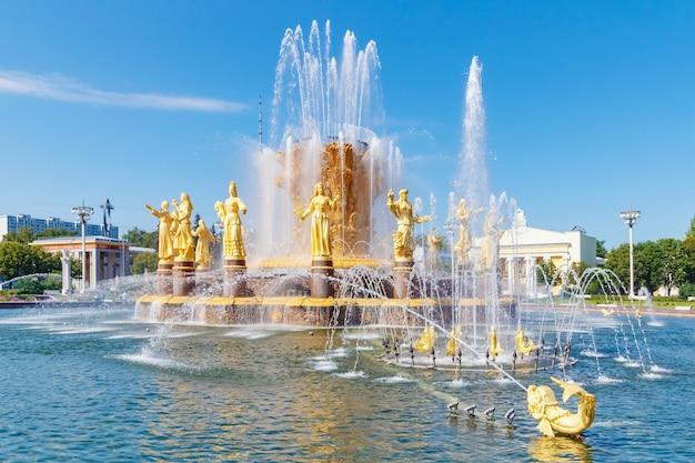 Widok na powierzchnię wody i złote figury fontanny przyjaźni narodów w parku vdnh w moskwie w słoneczny letni dzień na tle błękitnego nieba