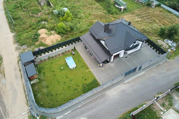 Widok na prywatny dom z zielonym podwórkiem i małym basenem na trawniku.