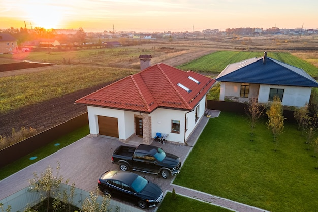 Widok na prywatny podmiejski dom z zaparkowanymi samochodami na podwórku.