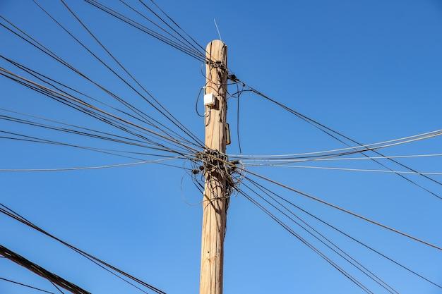 Widok na przewody elektryczne na słupie w słoneczny dzień.