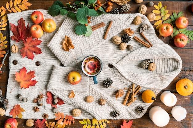 Widok na romantyczną jesienną kompozycję dojrzałych owoców, liści, przypraw, gorącej herbaty, świec, orzechów i szyszek na wełnianym swetrze