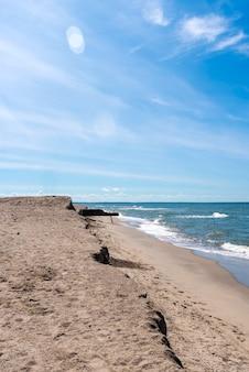 Widok na rozciągającą się w oddali linię brzegową, błękitne morze i piaszczystą plażę
