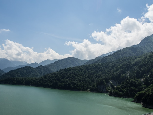 Widok na rzekę i lasy na górze na błękitnym niebie