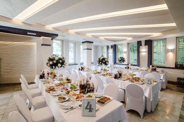 Widok na salę restauracyjną. świąteczny stół ozdobiony kompozycją kwiatów, zieleni, świec w sali weselnej. stół nowożeńców przykryty obrusem.