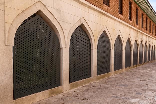 Widok na ścianę meczetu z dużymi zdobionymi oknami i drewnianymi żaluzjami na dziedzińcu w turcji, alanya