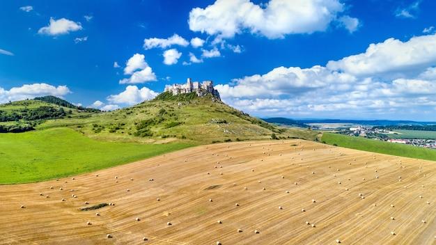 Widok na spiski hrad i pole z okrągłymi belami na słowacji, europa środkowa