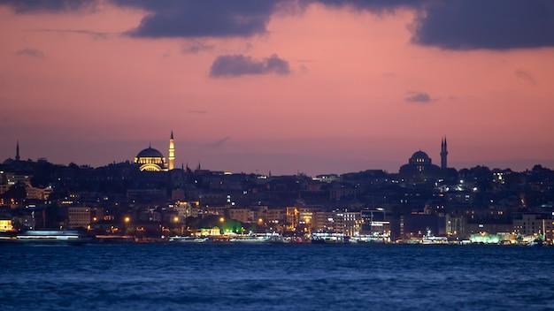 Widok na stambuł nocą, iluminacje wielokrotne, budynki i meczety, cieśnina bosfor na pierwszym planie, turcja