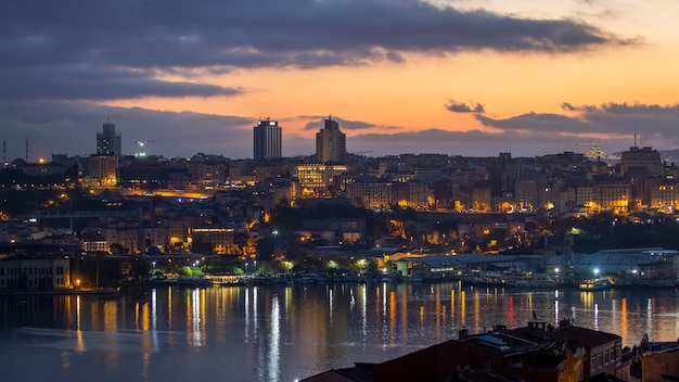 Widok na stambuł nocą, iluminacje wielokrotne, budynki niskie i wysokie, cieśnina bosfor na pierwszym planie, turcja