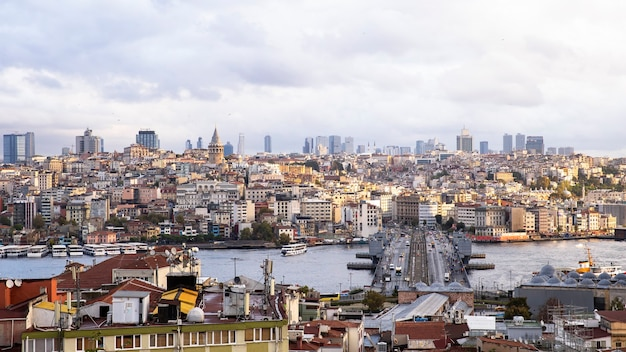 Widok na stambuł przy pochmurnej pogodzie, cieśnina bosfor dzieląca miasto na dwie części, wiele budynków, most z samochodami, turcja