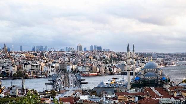 Widok na stambuł przy pochmurnej pogodzie, cieśnina bosfor dzieląca miasto na dwie części, wiele budynków, nowy meczet i most z samochodami, turcja