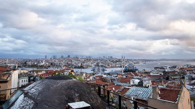 Widok na stambuł przy pochmurnej pogodzie, cieśnina bosfor dzieląca miasto na dwie części, wiele budynków, nowy meczet, turcja