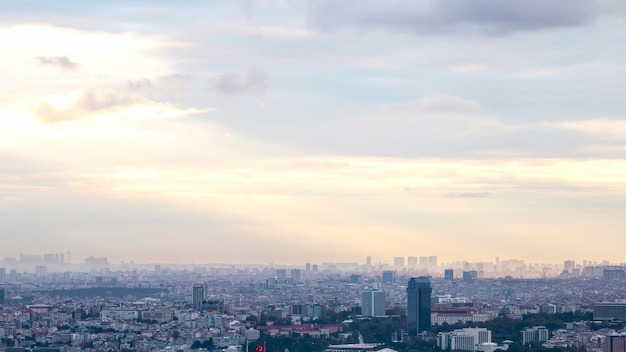 Widok na stambuł przy pochmurnej pogodzie, wiele niskich i wysokich budynków, mgła i światło słoneczne przebijające się przez chmury, turcja