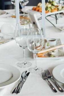 Widok na stół weselny przykryty białym obrusem z pustymi szklankami, talerzami i sztućcami. na stole podawane są przekąski.