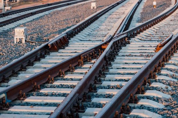 Widok na szyny, podkłady betonowe i kopiec z pokruszonego kamienia. tory kolejowe.