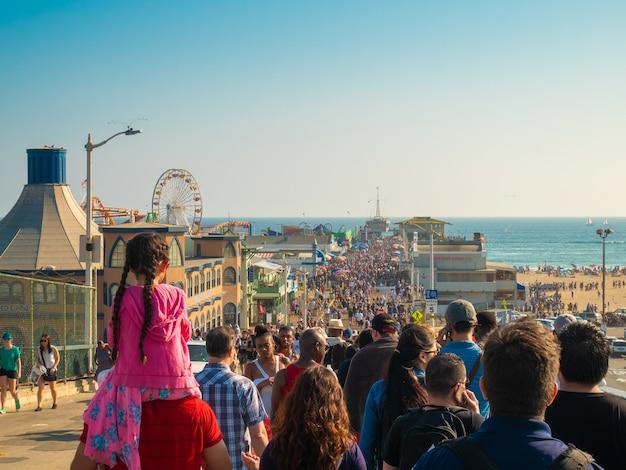 Widok na tłum spacerujący latem przy molo w santa monica.