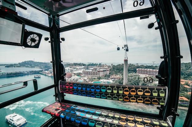 Widok na turkusowe morze ze statkiem i wyspą od kolejki linowej do sentosa w singapurze