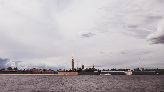 Widok na twierdzę piotra i pawła i newę w dzień. unikalny krajobraz miejski centrum sankt petersburga. centralne zabytki miasta. najlepsze miejsca turystyczne w rosji. stolica imperium rosyjskiego