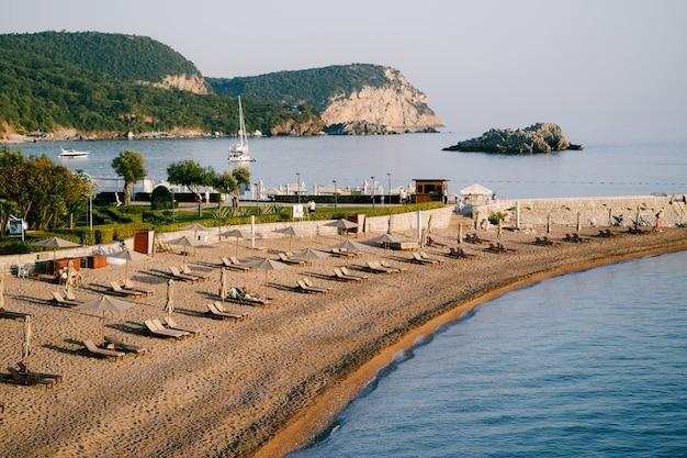 Widok na wąską plażę z leżakami i parasolami na powierzchni wyspy sveti stefan