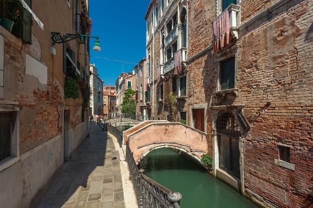 Widok na wąski kanał z łodziami i gondolami w wenecji, włochy. wenecja to popularna miejscowość turystyczna w europie