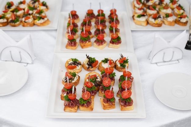 Widok na wesele lub bankiet z smacznymi warzywami i kanapkami z kiełbaskami lub tosty z pomidorami i zielenią na białym stole z serwetkami.