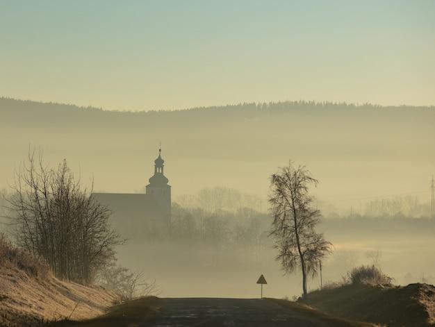 Widok na wiejską drogę i kościół w tle na dolnym śląsku, polska