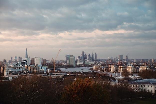 Widok na wieżowce londynu i tamizy z punktu widokowego na greenwich o zachodzie słońca