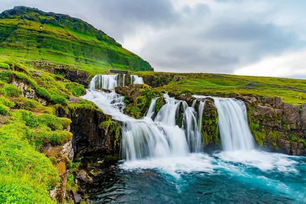 Widok na wodospady kirkjufellsfoss na górze kirkjufell w letni deszczowy dzień w grundarfjordur w zachodniej islandii