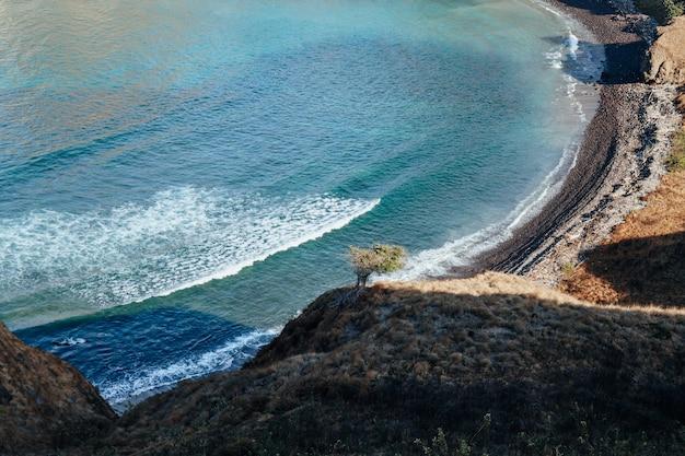 Widok na wybrzeże ze spokojnymi falami ze szczytu wzgórza na wyspie padar