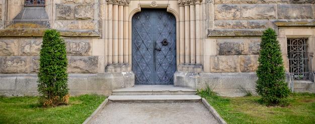 Widok na zabytkowe drzwi i zamek z podwórka