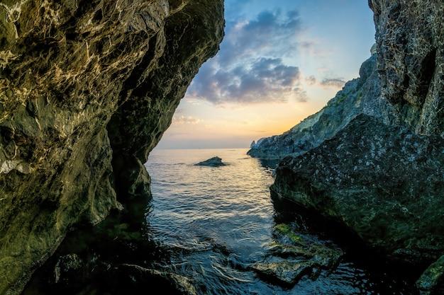 Widok na zachód słońca morze i plażę, wulkaniczną skałę, piasek i kamyczki, wulkaniczny bazalt jak na islandii.