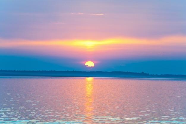 Widok na zachód słońca nad jeziorem ze ścieżką światła słonecznego i sylwetkami łodzi (świtiaź, ukraina)