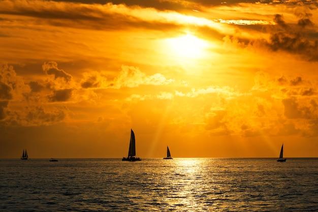 Widok na żaglówki na morzu o zachodzie słońca
