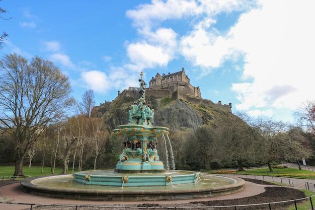 Widok na zamek w edynburgu i fontannę rossa z ogrodów princes street w edynburgu w szkocji
