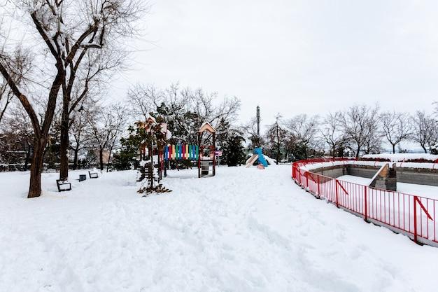 Widok na zaśnieżony miejski plac zabaw.