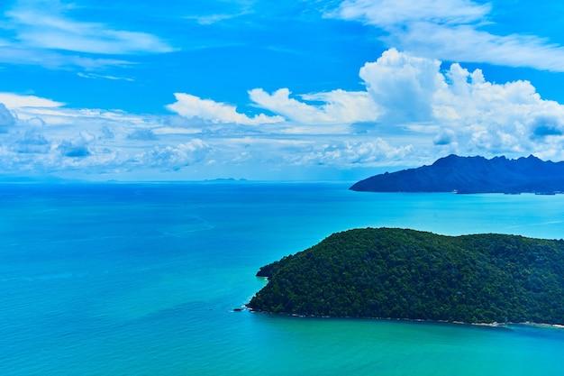 Widok na zieloną tropikalną wyspę na oceanie z okna samolotu.