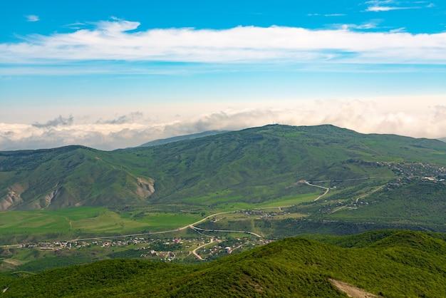 Widok na zielone góry i wioski w dolinie. panorama szerokokątna